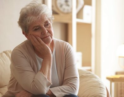Depressed elderly woman sitting on lounge at home